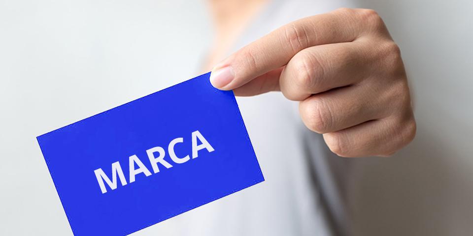 """Pessoa segurando um cartão na ponta do dedo escrito """"marca"""""""